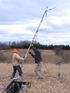 Photo: two people raising a telemetry tower in a field