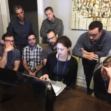 Photo: scientists gathered around a laptop computer