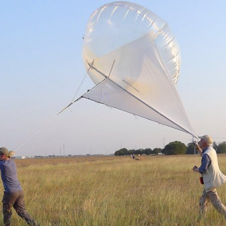 Photo: scientists carrying Helikite across a grassy field