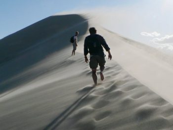 Photo: People walking along the ridge of a windy sand dune
