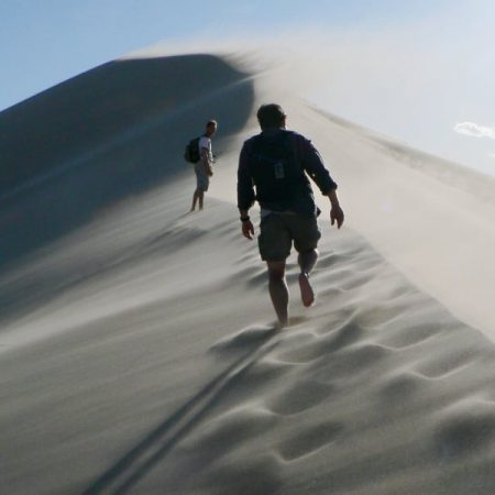 Photo: People walking along the ridge of a windy sand dune