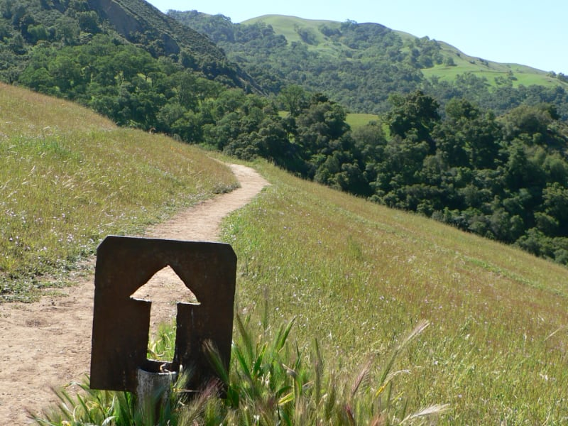 Photo: Rustic arrow sign pointing up a hillside trail