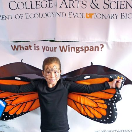 Photo: girl in butterfly costume posing in front of a wingspan banner